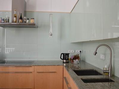 Glasfront-Küche, Edelstahl-Wasserhahn und Ceran-Kochfeld